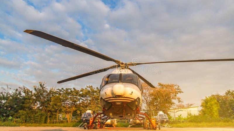 Helikopter in het parkeerterrein of de baan die op onderhoud met zonsopgangachtergrond wachten, schemeringhelikopter op de heliha stock foto's