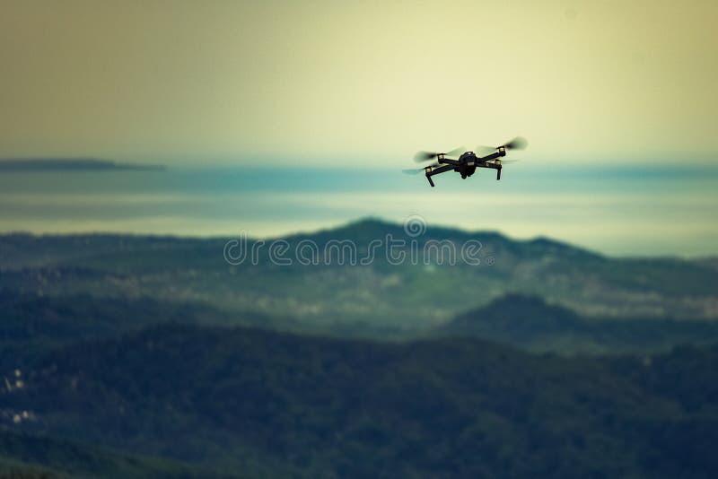 Helikopter i flykten över bergen på horisonthavssolnedgången royaltyfria bilder