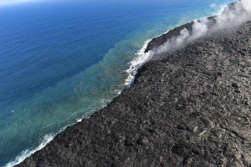 Helikopter luchtmening die van lava de oceaan en de stoom, Groot Eiland, Hawaï ingaan stock afbeelding