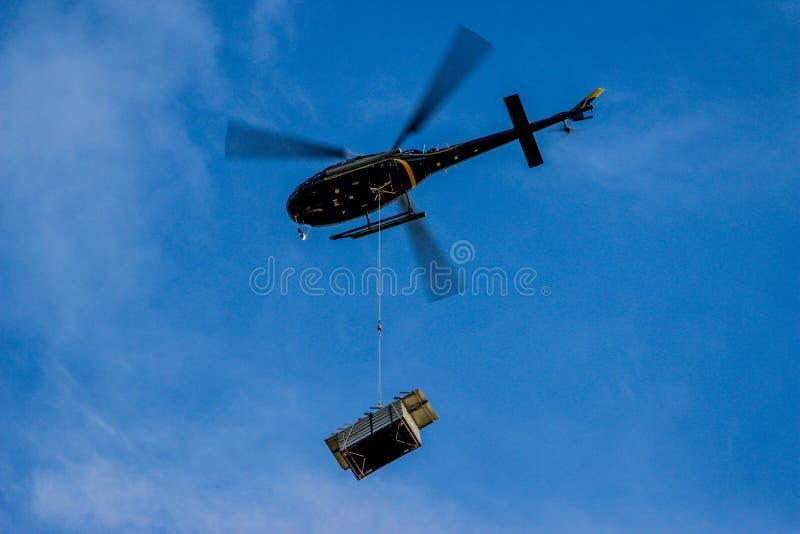 Helikopter met vage bladen die ladingen dragen royalty-vrije stock afbeeldingen
