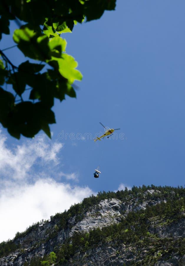 helikopter niesie małego ładunku ładunek nad góry w Lauterbrunnen dolinie zdjęcia royalty free