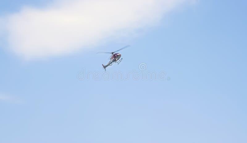 Helikopter op duidelijke blauwe hemelachtergrond met wolk stock foto