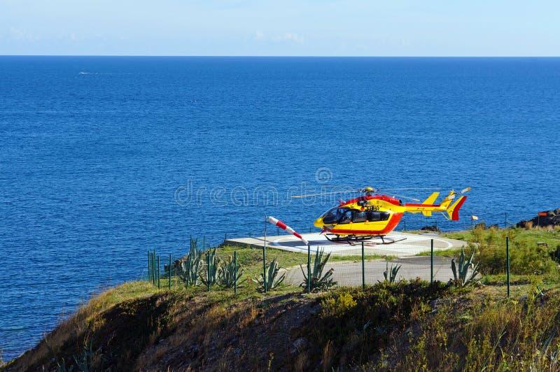 Helikopter på ett landningområde med havet i bakgrund arkivbild