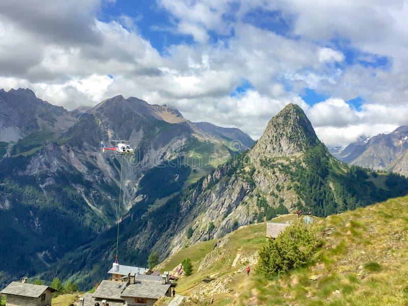 Helikopter przenosi materiał budowlanego w Alps blisko Courmayeur Włochy zdjęcie stock