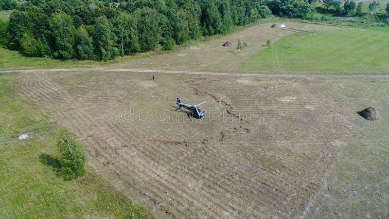 Helikopter przyjeżdżający na zieleni polu Helikopter lądował na żółtej trawie, chmurny dzień Latający truteń i zielony pszeniczny zdjęcia royalty free