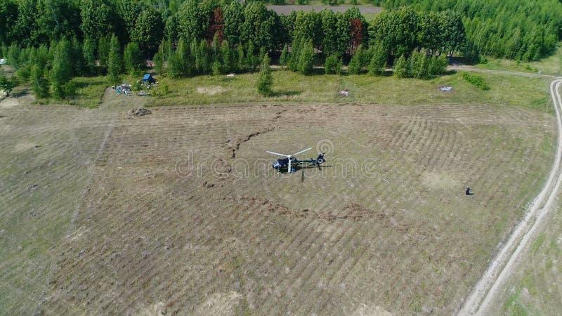 Helikopter przyjeżdżający na zieleni polu Helikopter lądował na żółtej trawie, chmurny dzień Latający truteń i zielony pszeniczny obraz royalty free