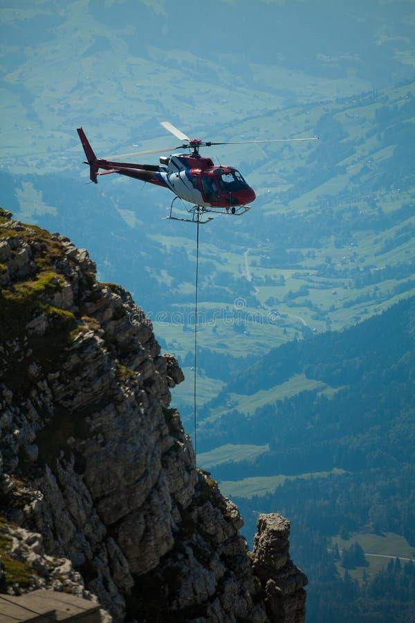 Helikopter som transporterar konstruktionsgods till konstruktionsplatsen i de schweiziska alpesna arkivfoto