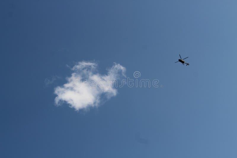 Helikopter wojskowy i biała chmura na niebieskim niebie fotografia stock