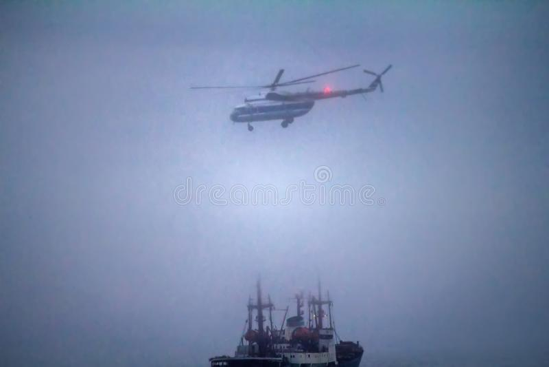 Helikopter wykonuje ładownicze operacje na icebreake w mgle obrazy royalty free