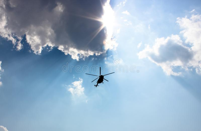 Helikopterflyg i himlen bland strålarna av solen royaltyfri bild