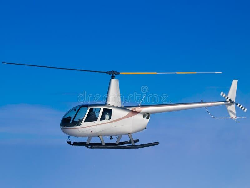 Helikopterflyg i sida för blå himmel arkivfoton