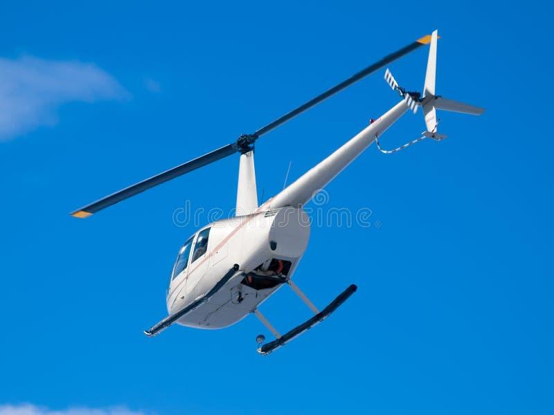 Helikopterflyg i sikt för blå himmel från under och bakom arkivbild