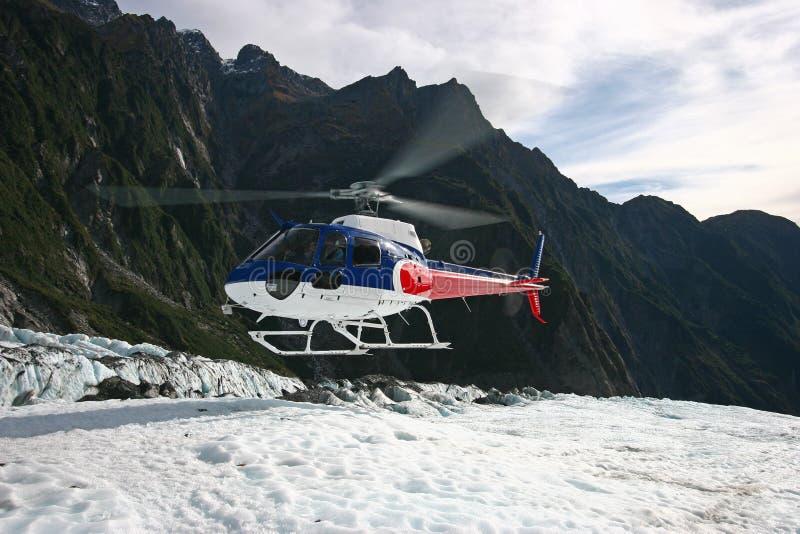 Helikopterlandning på is på bergöverkant arkivbild