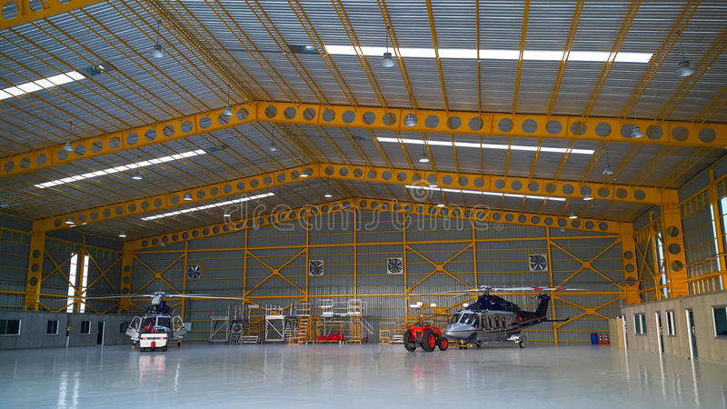 Helikopterparkering i hangar och förbereder sig för flyga iväg servicelaget arkivfoto
