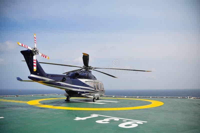 Helikopterparkering på helideck och väntande passagerare Helikopterlandning och väntande på marktjänst royaltyfria bilder