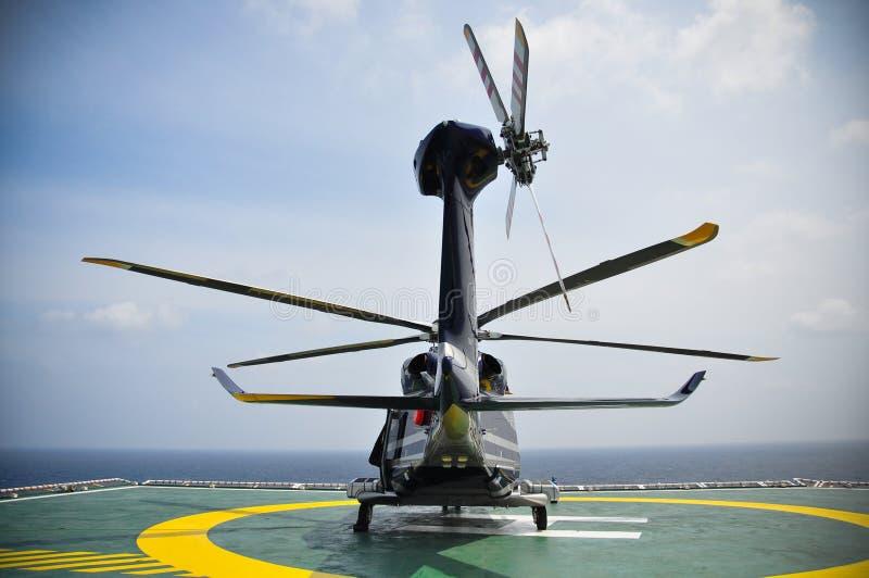 Helikopterparkering på helideck och väntande passagerare Helikopterlandning och väntande på marktjänst arkivfoto