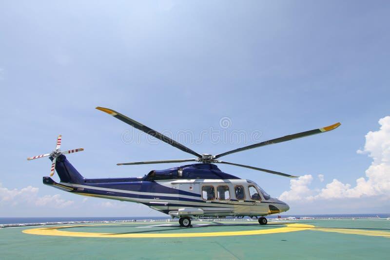 Helikopterparkeringslandning på den frånlands- plattformen Helikopteröverföringsbesättningar eller passagerare till arbete i från royaltyfri bild