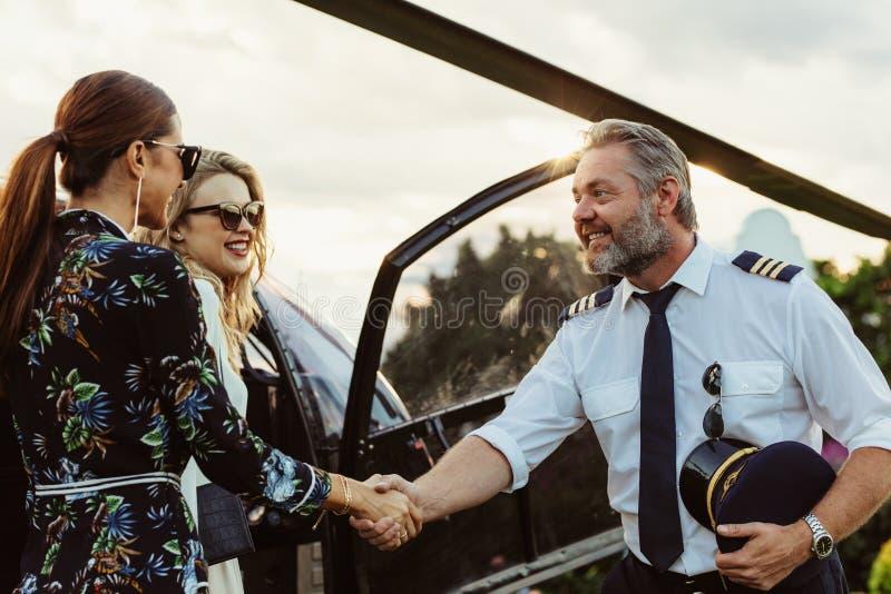 Helikopterpilot som skakar händer med två kvinnor royaltyfria foton