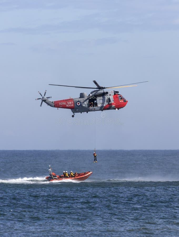 Helikopterreddingsdienst op zee stock afbeelding