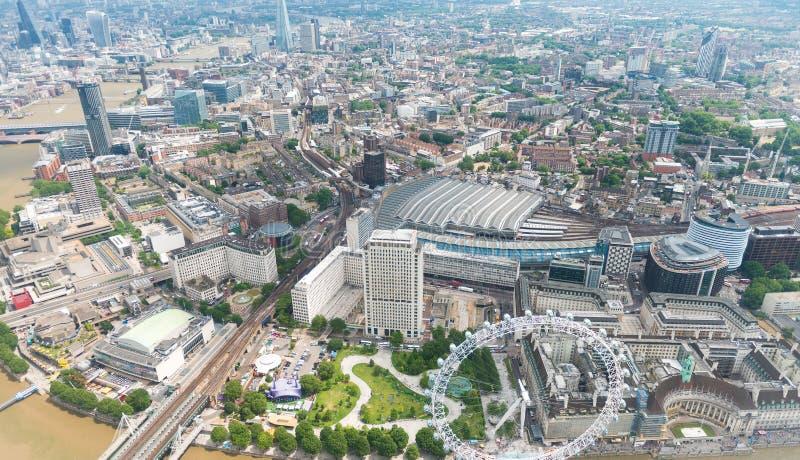 Helikoptersikt av London med byggnader och flodThemsen arkivbild