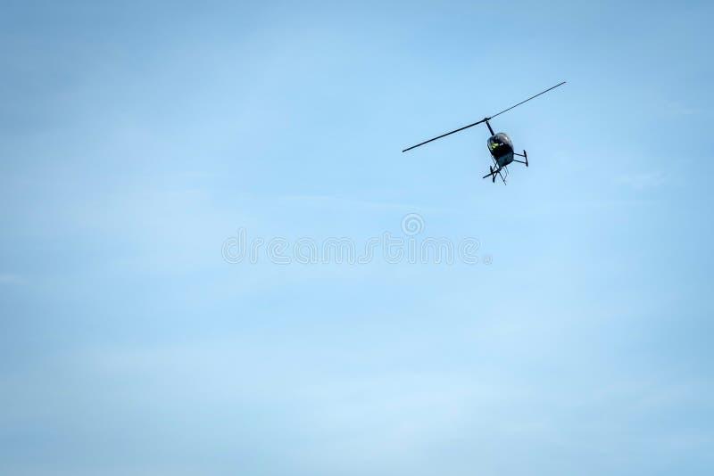 Helikoptersilhouet op een lichtblauwe hemelachtergrond stock afbeeldingen