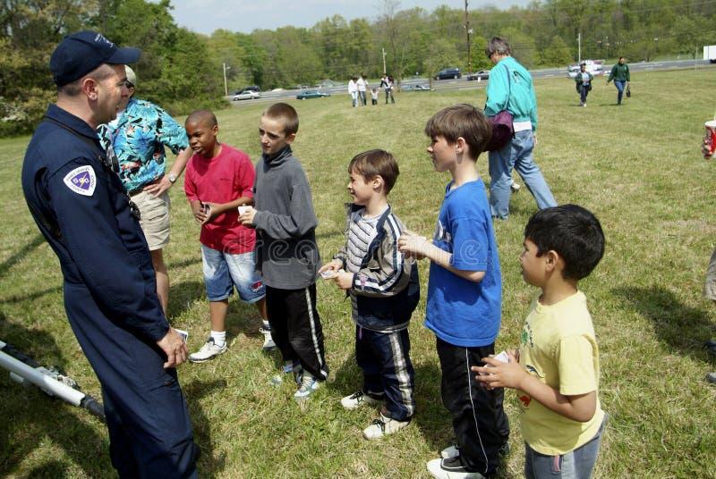 Helikopteru policyjnego pilot opowiada kilka dzieci i wyjaśnia jak helikopter pracuje zdjęcie stock