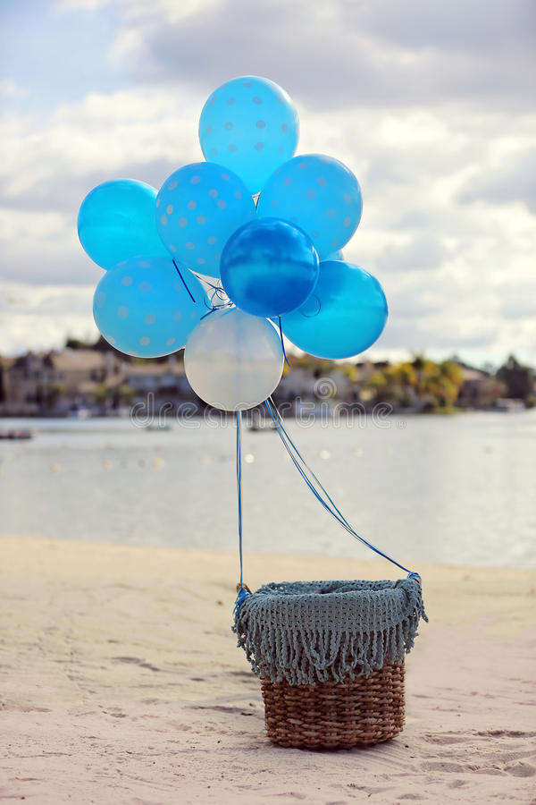 Helium balloon basket. A basket tied with helium balloons front of a private lake for baby photography royalty free stock photography