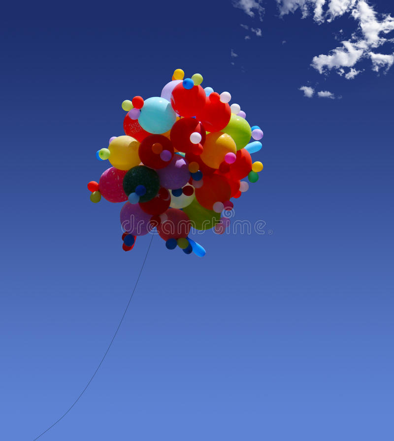 Helium balloons. Flying on blue sky royalty free stock images