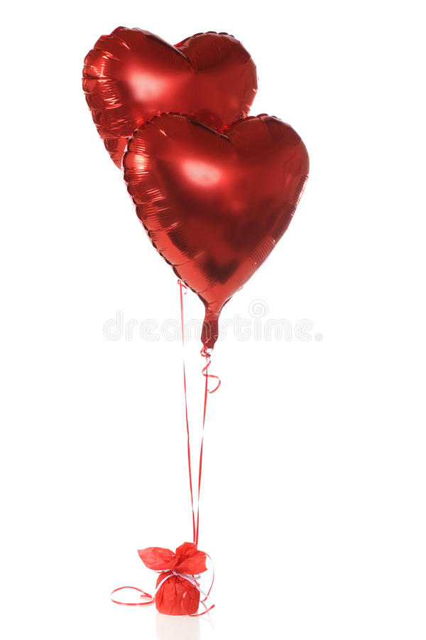 Helium Hearts. Two red, heart-shapped, helium-filled ballons anchored with red ribbons. Isolated on white stock image