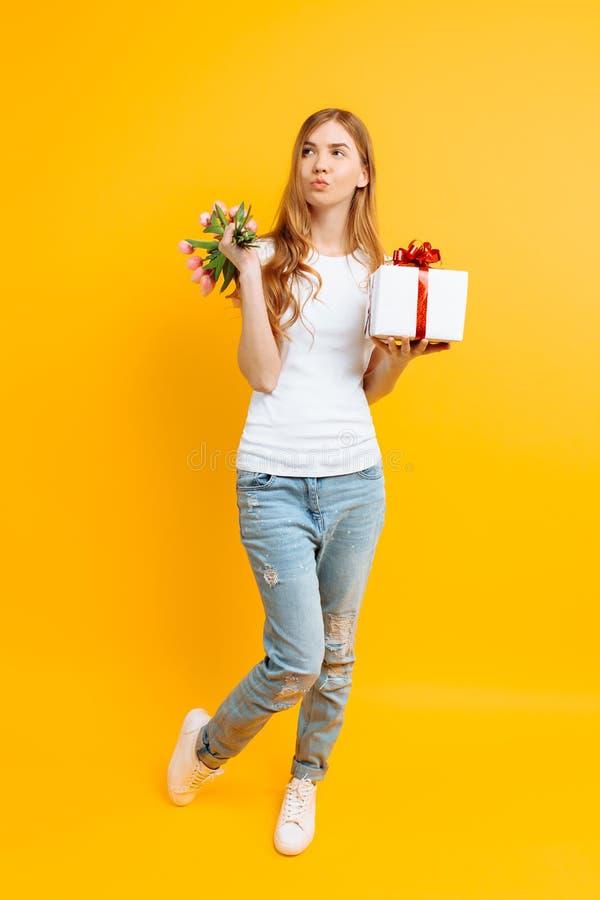Hellång fundersam flicka med en bukett av härliga blommor och en gåvaask på en gul bakgrund royaltyfri foto