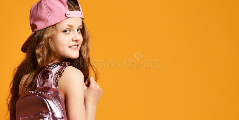 Hell?ng inomhus st?ende av en ton?ringflicka i en gul kjol gymnastikskor och ett lock med en glamor?s ryggs?ck royaltyfri foto
