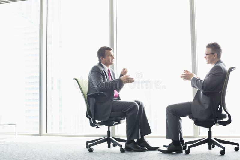 Hellång sidosikt av affärsmän som diskuterar, medan sitta på kontorsstolar vid fönstret royaltyfri foto