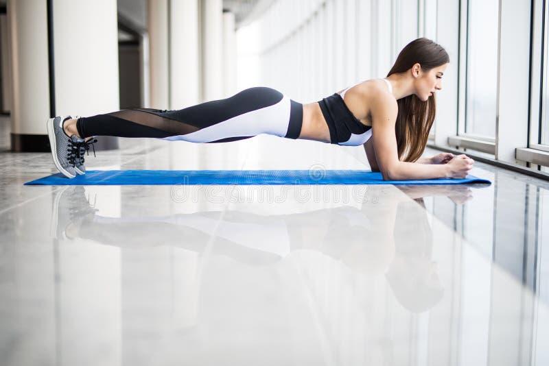 Hellång sidosikt av den unga härliga kvinnan i sportswearen som gör plankan, medan stå framme av fönster på idrottshallen royaltyfri foto