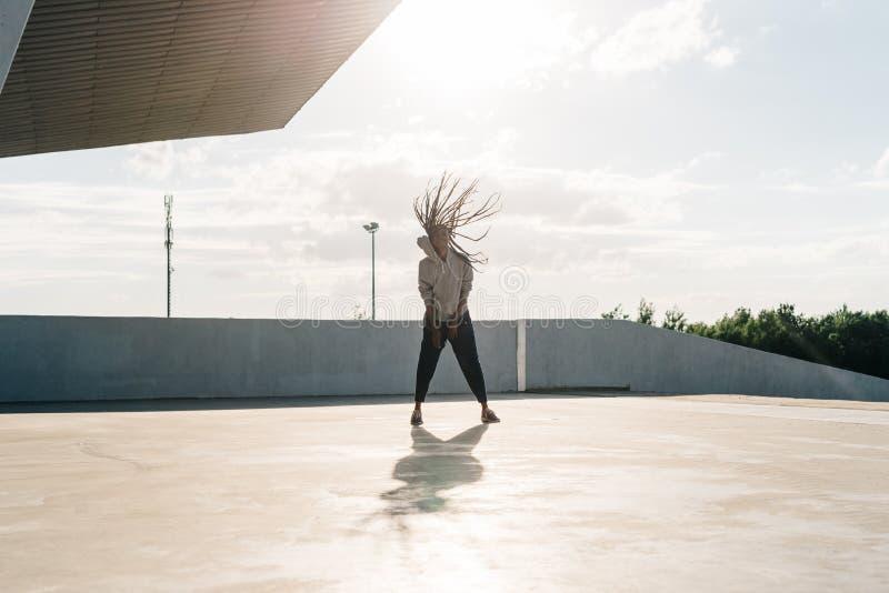 Hellång sikt av den unga afrikanska sportive kvinnan som har gyckel Hon skakar hennes huvud i solsignalljus arkivfoton