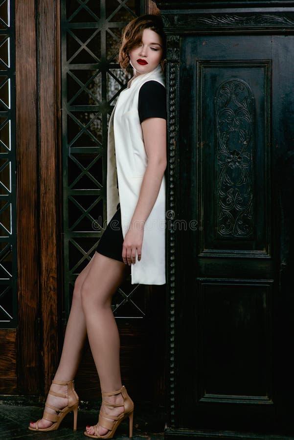 Hellång stående av barn, härlig ledsen kvinna med kort brunt hår med stilfullt smink i svart klänning och vitwaistcoat royaltyfria bilder