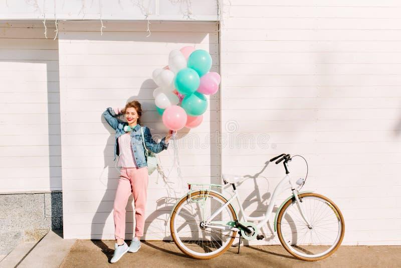 Hellång stående av den aktiva gladlynta flickan med partiballonger som är klara att cykla ritt i solig morgon stilfullt barn arkivfoto