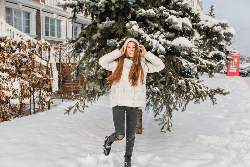 Hellång stående av den avkopplade blonda flickan i svarta flåsanden som dansar på den snöig gatan med leende Utomhus- foto av rol royaltyfri foto