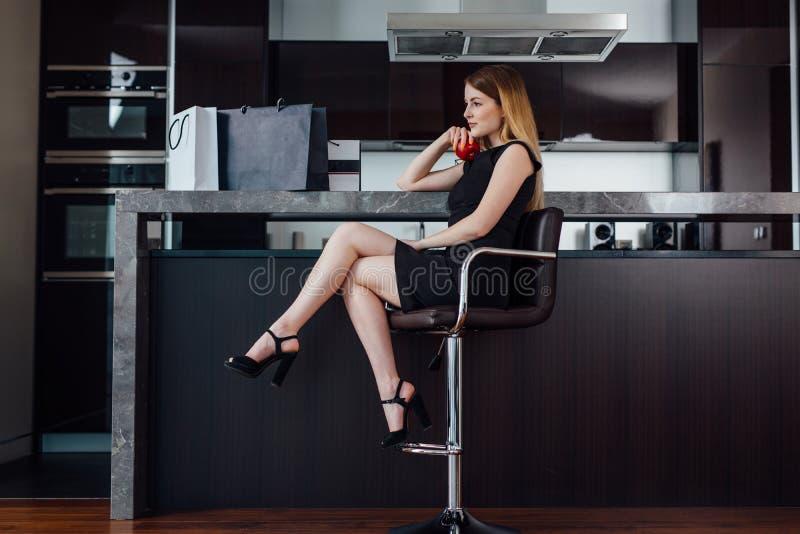 Hellång stående av den eleganta kvinnan med ganska hår som bär den svarta klänningen och höga häl som in sitter på en stångstol arkivbilder