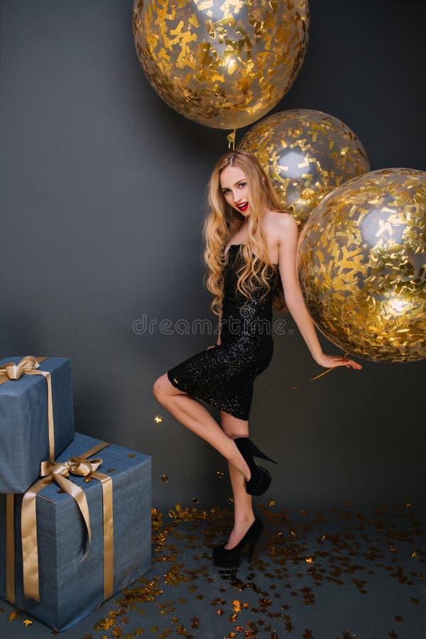 Hellång stående av den förtjusande födelsedagflickan med guld- ballonger som firar något Inomhus foto av nöjt royaltyfria foton