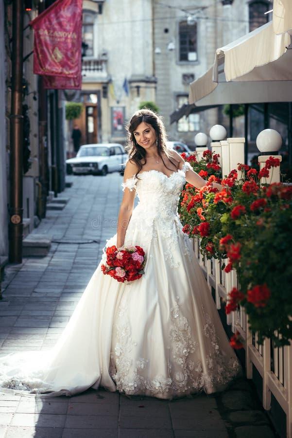 Hellång stående av den härliga brunettbruden i den långa bröllopsklänningen som rymmer den röda och rosa bröllopbuketten arkivfoton