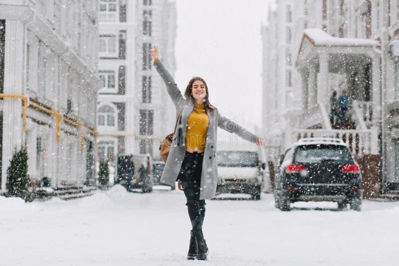 Hellång stående av den inspirerade kvinnliga modellen i det stilfulla laget som poserar med nöje i vinterstad Utomhus- foto av gl royaltyfria foton