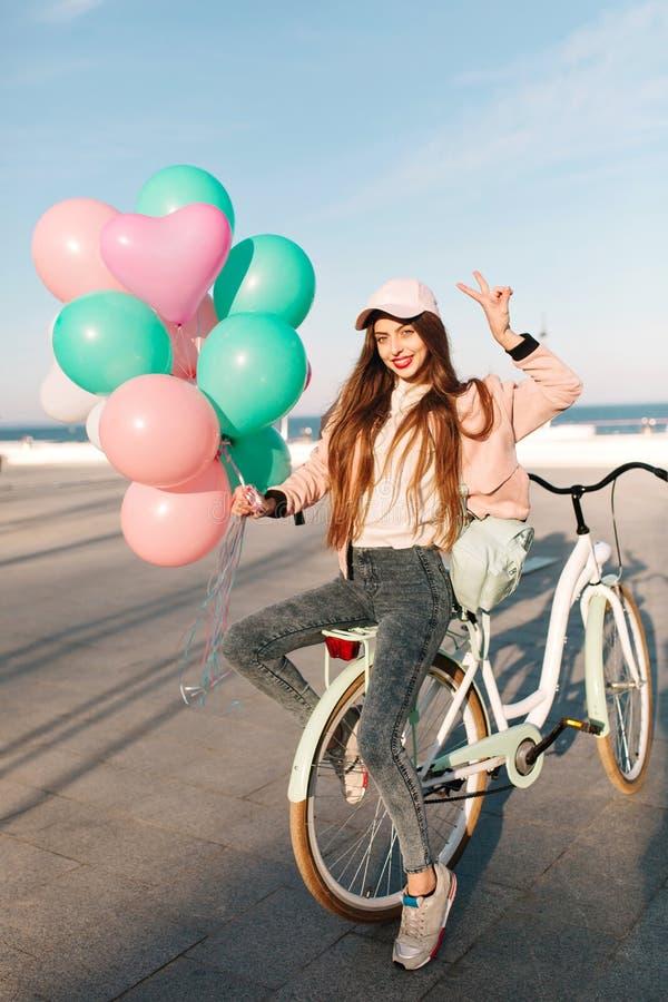 Hellång stående av den slanka flickan i locket och moderiktiga gymnastikskor som sitter på cykeln på havspir i solig morgon h?rli fotografering för bildbyråer