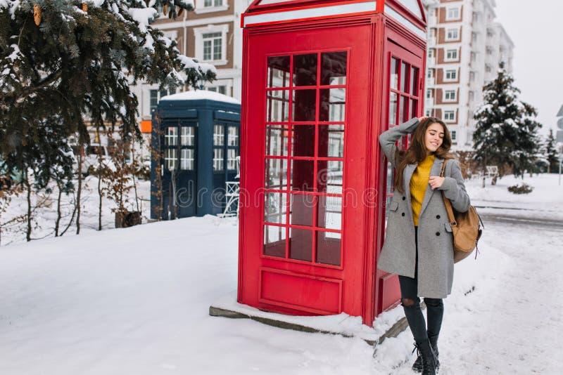 Hellång stående av den storartade unga kvinnan i det stilfulla laget som poserar med nöje nära brittiskt telefonbås Foto av royaltyfri bild