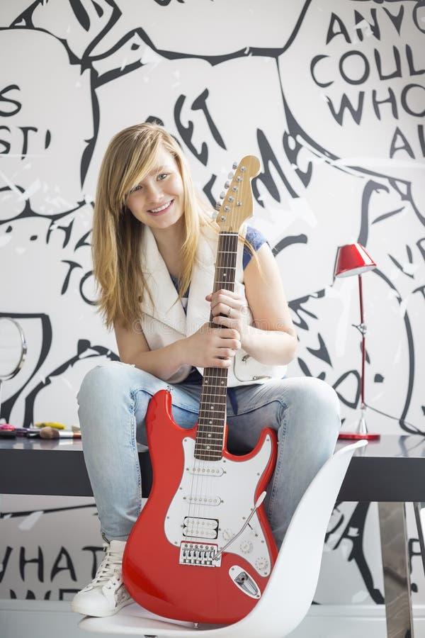 Hellång stående av den tonårs- flickan med sammanträde för elektrisk gitarr på studietabellen hemma royaltyfria foton
