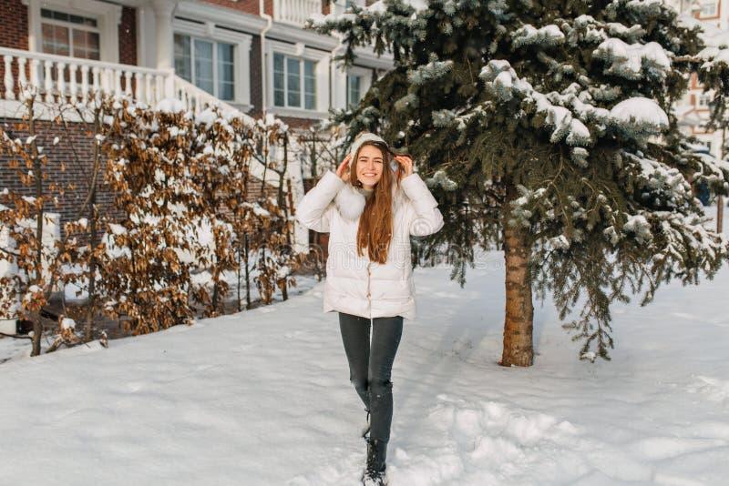 Hellång stående av den trendiga långhåriga damen som poserar bredvid hus nära grönt snöig träd Utomhus- foto av arkivfoto