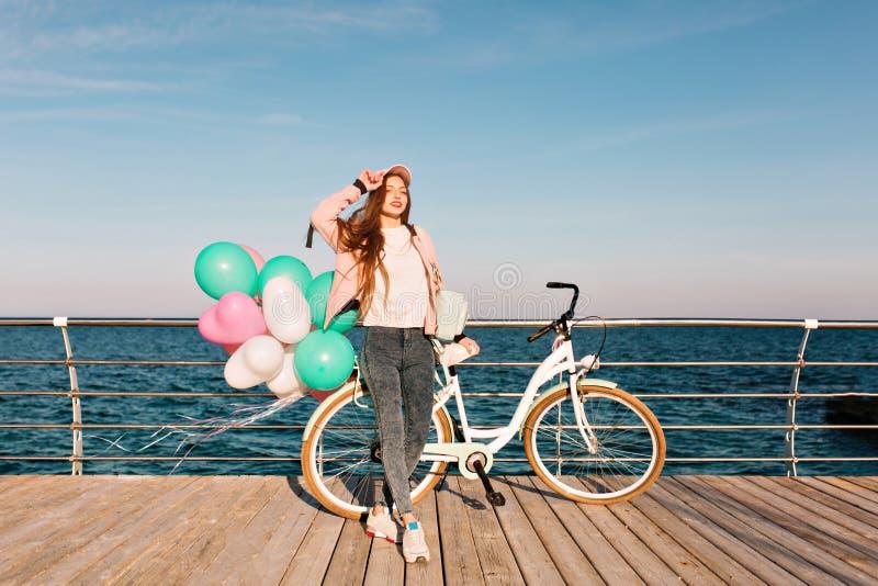 Hellång stående av det ursnygga kvinnliga cyklistanseendet på pir på havsbakgrund i hennes födelsedag charma fotografering för bildbyråer