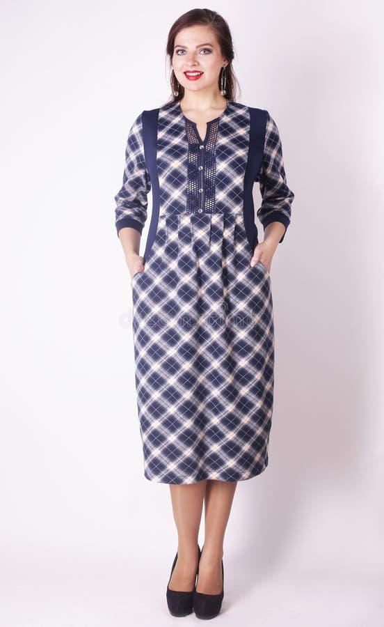 Hellång stående av en härlig kvinna i en pläddagklänning Plus format royaltyfria foton