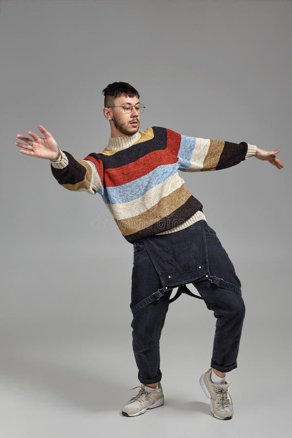 Hellång stående av en rolig grabbdans i studio på en grå bakgrund arkivfoto