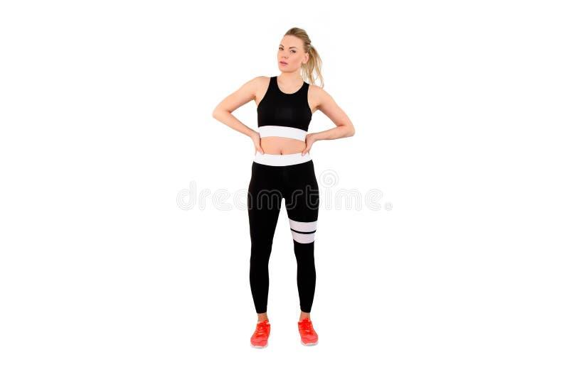 Hellång stående av en sportkvinna som poserar med hennes händer på höfter som isoleras på vit bakgrund - bild arkivbilder