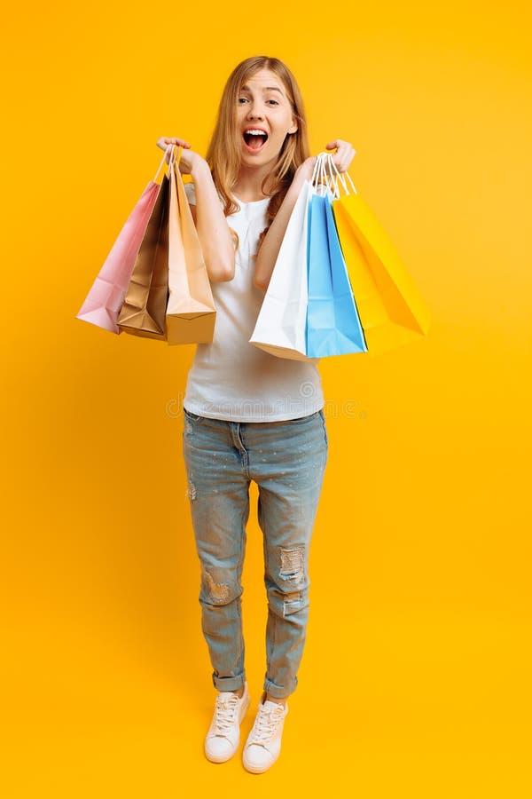 Hellång stående av en ung chockad kvinna som är lycklig, når att ha shoppat med mång--färgade påsar, på en gul bakgrund arkivfoto